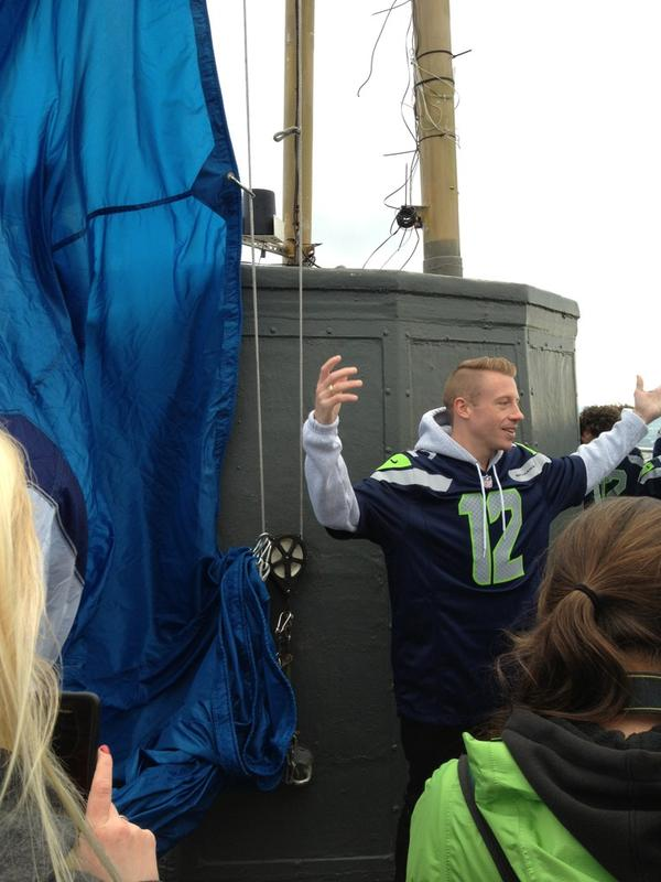 Macklemore helping rais the 12th man flag atop the Space Needle.